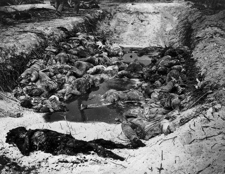 WORLD WAR II. The Pacific Campaign. November 1943. Tarawa atoll (occupied by the Japanese). Japanese soldiers killed during the American attack against the atoll, being buried in trenches built by the Americans.