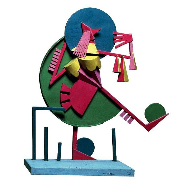 Fortunato Depero La toga e il tarlo, 1914, MART – Museo di Arte Moderna e Contemporanea, Rovereto (Trento). Un po' scultura e un po' giocattolo, questo personaggio in cartone e legno policromi, è un perfetto esempio di quei tipici prodotti futuristi difficilmente classificabili secondo rigide categorie.