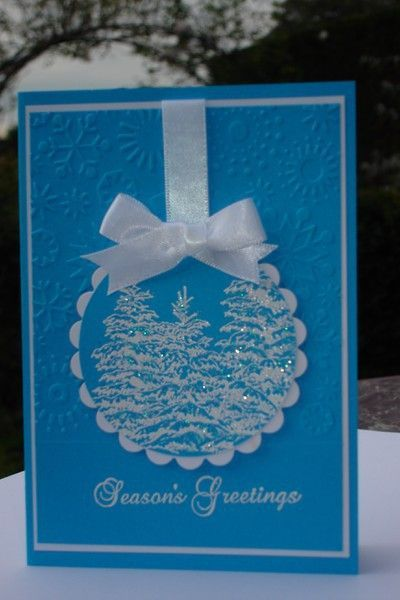 handmade Christmas card from Lecture d'un message  ... bright blue with white ... circle bauble hanging from a satin bow ... glittery heat embossed  trees ... embossing folder small snowflakes on background ...