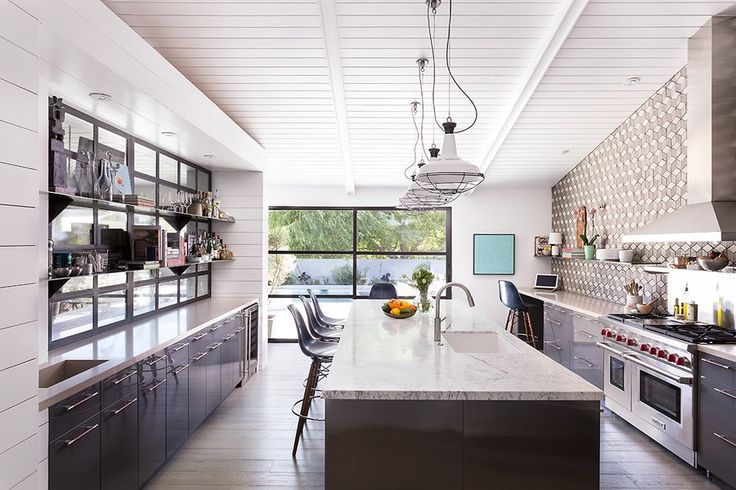 """Opening up the kitchen to the dining room turned a once solely functional room into a central hub. Rather than a traditional tile backsplash, the designers chose to install custom concrete tile by Arto Brick in an eye-catching geometric pattern. """"There is something about our kitchen that truly feels like you could spend the whole day there,"""" says Brown. """"The doors open out to the pool, so when we entertain, our guests always feel like they are engaged in the party, even if they're outdoors."""""""