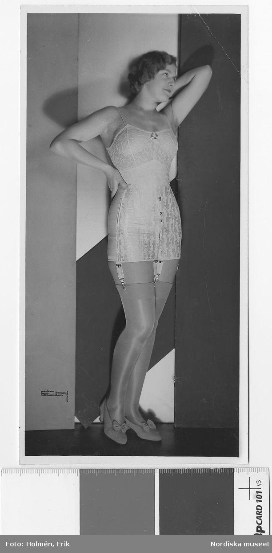 1931. Kvinna i korsett, strumpor och högklackade skor med rosett. Nordiska Kompaniet. Fotograf: Erik Holmén