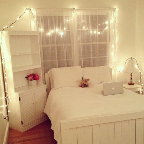 I love this bedroom. Simple clean white furniture, christmas lights, beautiful flowers and the odd composition of the furniture