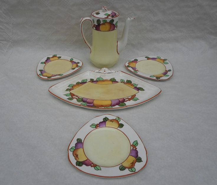 A 1920s Burleigh Ware part sandwich and coffee set, designed by Charlotte Rhead in the 4102 pattern, comprising a fan-shaped dish, three triangular plates and a coffee pot, featuring a tube-lined decoration of fruits and leaves, printed and tubed marks to bases, with the coffee pot bearing Charlotte's own signature