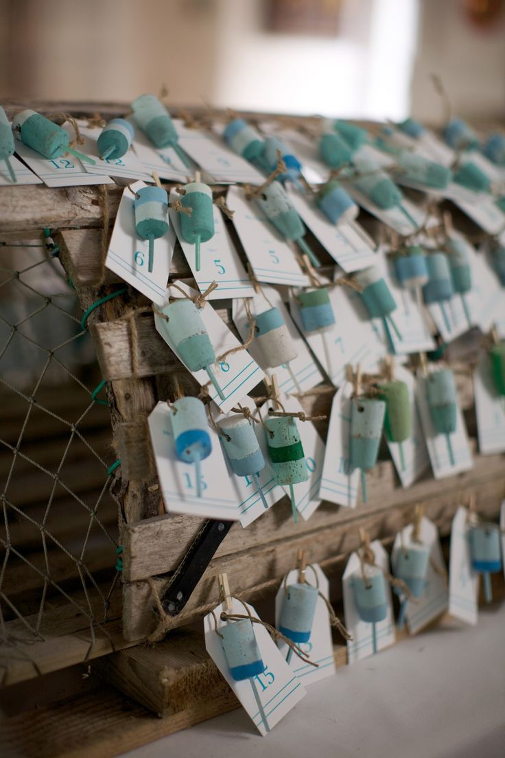 Lobster trap as a display for wine cork buoys (=Escort cards) - Peaks Island, Maine Wedding from Lara Kimmerer Photography