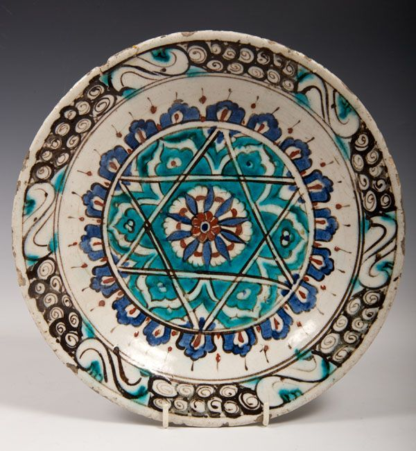 Early Iznik tin glazed pottery dish with blue, red and black floral and star motifs, 27cm