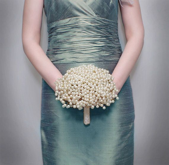 A pearl bouquet is a fun alternative to a traditional bouquet. In this example, the bridesmaid is carrying a small pearl bouquet in ivory.