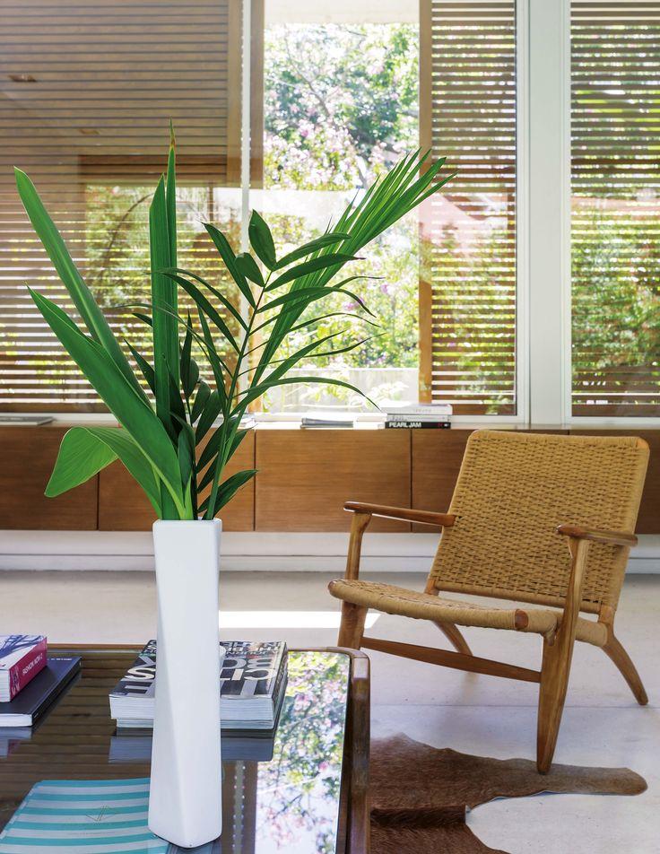 Living moderno con sillones individuales heredados y reciclados, y por afuera parasoles móviles que actúan como rejas, en aluminio pintado imitación madera.