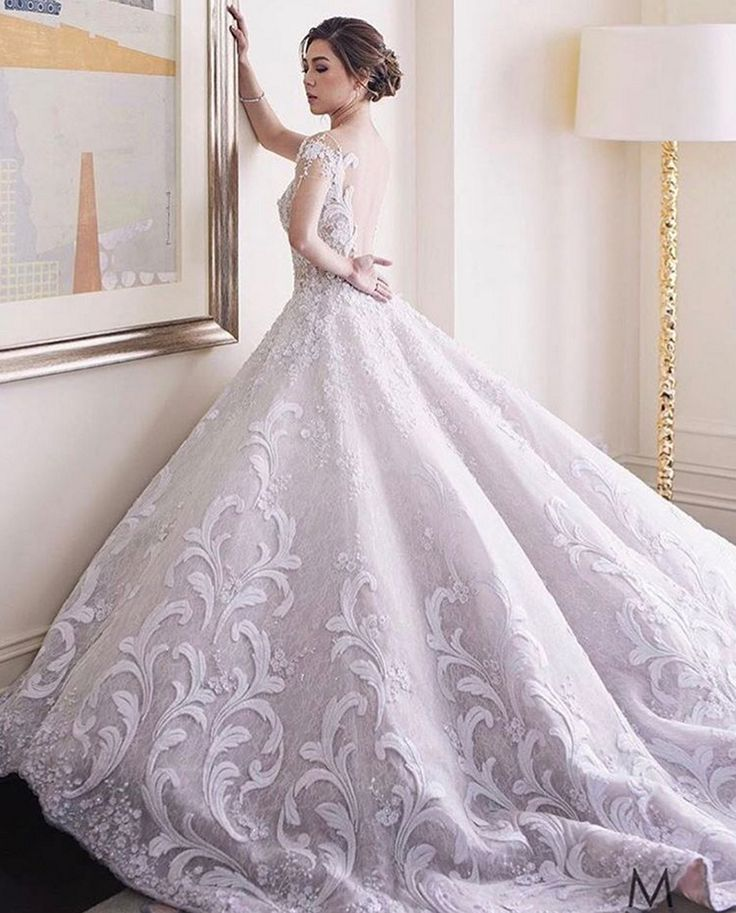 White backless wedding dress with gorgeous full skirt // Filipino designer Mak Tumang studied interior design before delving into fashion in the Philippines. His love of opulent costumes and architecture influences his designs and this can be seen in his gowns which are rich in elaborate detail.