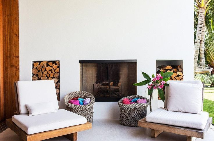 "Modern built-in outdoor fireplace with platform chairs and baskets of towels ready for guests to grab. See the full home tour here ""Inside the Breezy Palm Beach Home of Kelly Klein"" on the One Kings Lane Style Guide!"