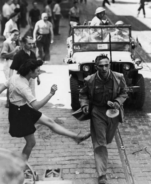 French girl vents anger by kicking at a passing German prisoner on his way to confinement after being captured. September 26, 1944.