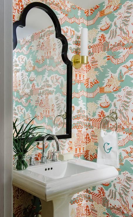 Clad in Thibaut Luzon Wallpaper, this charming blue and orange powder room is equipped with a black arched mirror mounted above a pedestal sink finished with a polished nickel gooseneck faucet lit by a brass wall sconce.