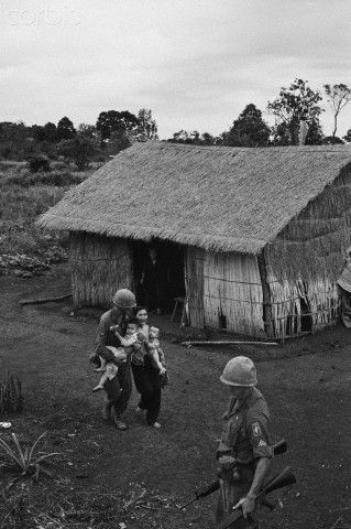 Vung Tau, South Vietnam: Viet Nam Scene. A paratrooper of the 173rd Airborne helps a weeping Vietnamese woman carry her children near Vung Tau, December 20th. The family was being evacuated because of the threat of a possible Viet Cong attack on a nearby U.S. artillery position.