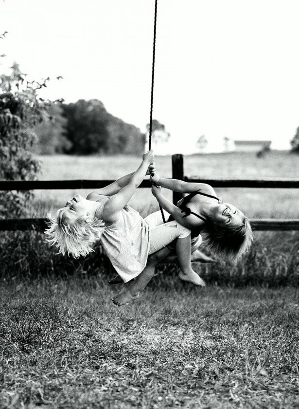 girls swinging on swing together by Gretchen Willis