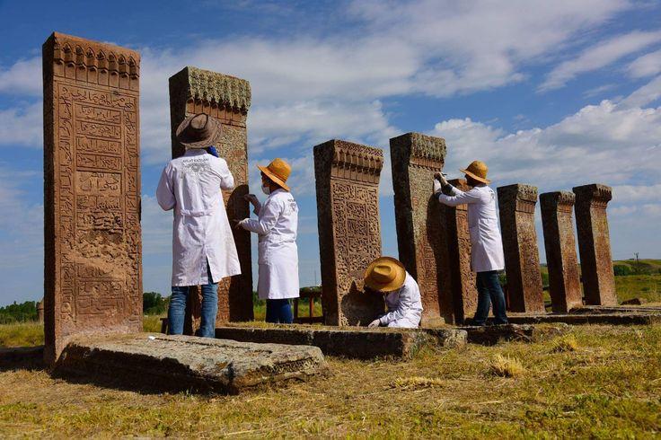 """Ahlat Selçuklu sinleri(mezar) düzenleniyor... Bitlis Ahlat'ta bulunan ve UNESCO Dünya Mirası Geçici Listesinde yer alan Selçuklu dönemine ait 'sin'lerle ilgili olarak, ortam koşullarının ideal düzeye getirilmesi, fotoğraflı-yazılı belgeleme, kuru temizlik, nemli temizlik, sağlamlaştırma, tamamlama ve rötuşları yapılıyor Van 100. Yıl Üniversitesi Sanat Tarihi Bölüm tarafından yapılan çalışmalar hakkında bilgi veren Bölüm Başkanı Prof. Dr. Recai Karahan, """"Bu yıl tahrip olan taşlara…"""