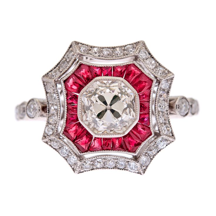 """Diamond & Ruby Platinum Art Deco Style Ring    Estate  Superbly hand crafted art deco style ring with a 1.01 carat old European cut diamond center stone. The diamond grades as H-I color, Vvs clarity and is very bright. The diamond is set in a mille grain edged platinum bezel, which almost appears to be an extension of the diamond. A scalloped border of custom cut red rubies makes the center diamond """"pop"""", followed by a frame of brilliant diamonds the shape of which mirrors the rubies."""