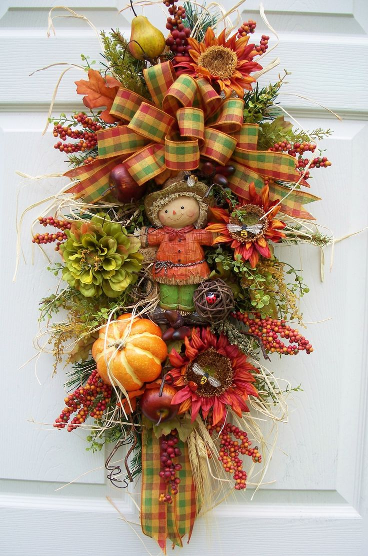 Scarecrow fall swag with wheat and raffia. http://www.timelessfloralcreations.com/