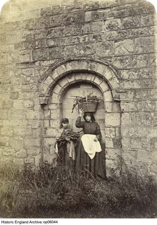 OP06044 Two girls with baskets of kindling wood standing in the blocked Norman doorway of Littleover Church, City of Derby. 1880 - 1900. Photographer: Richard Keane. Please click for more information, or to search our collections.