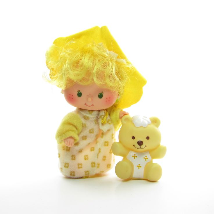 This vintage Strawberry Shortcake doll is Butter Cookie with her pet, Jelly Bear. Butter Cookie has yellow hair and green eyes and is one of Strawberry Shortcake's baby friends. She wears her original