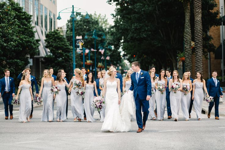 bride and groom head to the downtown church followed by their wedding party. bridesmaids in pale grey gowns carry bouquets of lavender,purple and pink flowers. the groomsmen wear navy suits with blue ties.