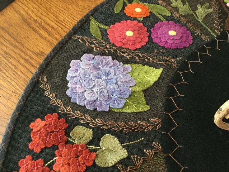 """Wool appliqué with crazy quilt stitching. Hand stitched by MaryAnnThom. Adapted from """"Flower Garden Crazy Tablemat """" by Primitive Gatherings."""