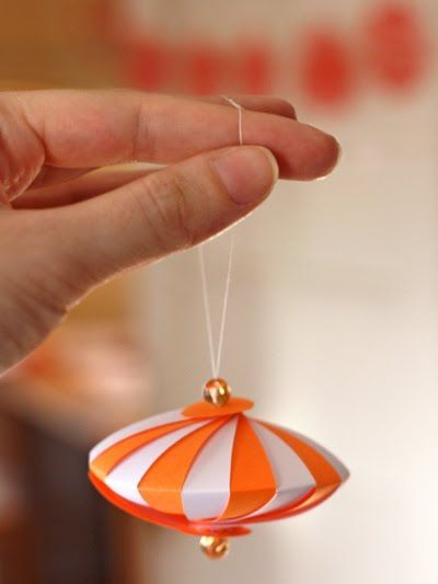 """Just thread through a bead, a penny-sized circle, 18 paper strips that are 3.5"""" long by 0.5"""" wide, and continue to the other side. The strip closest to the top circle will be farthest from the bottom circle. This makes a small ornament about 3"""" in diameter."""