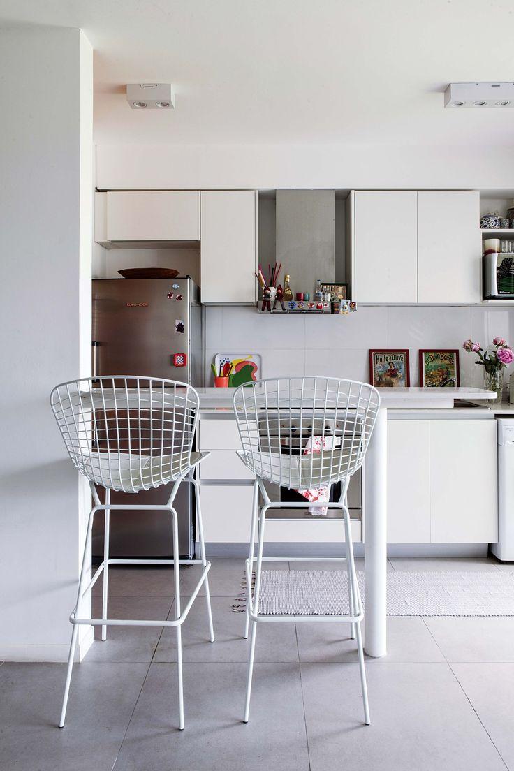 Desayunador en un pequeño duplex, resuelto con una mesa alta con tapa de Silestone y banquetas Bertoia.