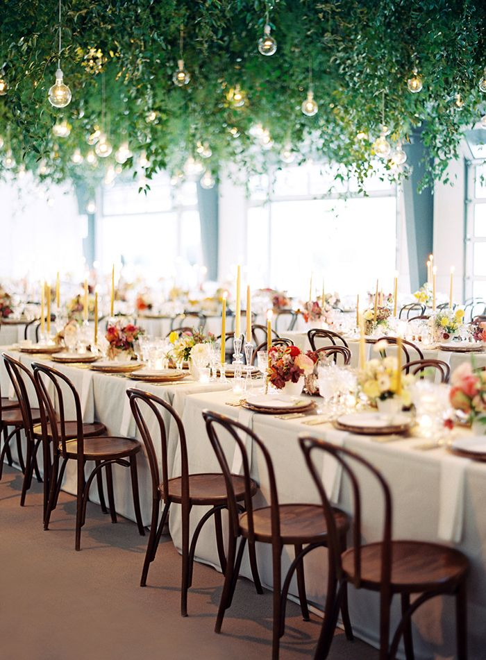 Greenery and Edison Bulb Floral Chandelier over Colorful Reception Tables