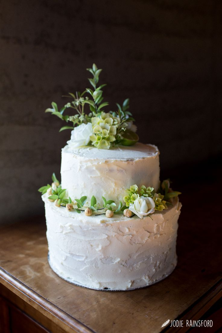 Fully iced two-tier Wanaka wedding cake with white flowers and fresh greenery
