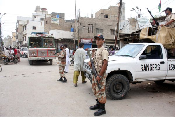 Rangers officials stand alert at a road in Liyari as after ceasefire heavy contingents of police and rangers were deployed at the entry and exit points at Liyari area in Karachi on Sunday, May 06, 2012.
