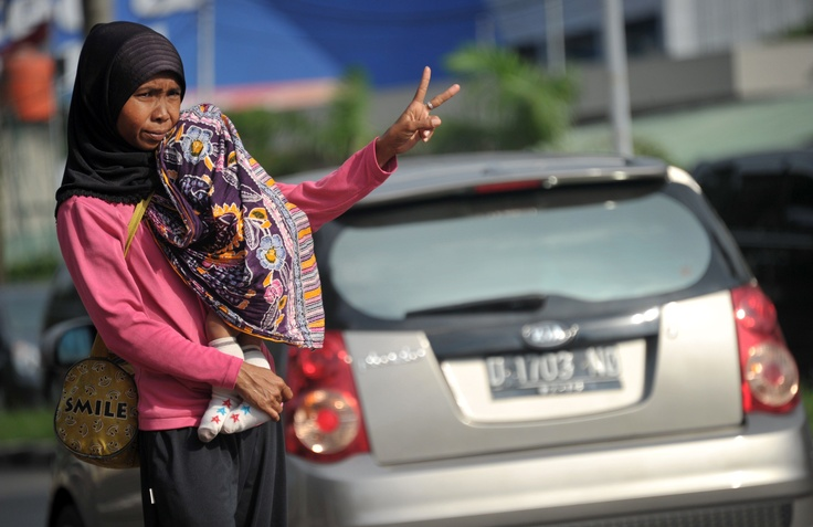 "Nuraeni, a ""3in1"" (one car with three passengers) traffic jockey, gestures as she offers her and her son to commuters in Jakarta on February 8, 2012.  Carpooling rules designed to ease Jakarta's notorious traffic jams have turned hitch-hiking into a stable but illegal profession for Indonesia's poor. For a small fee, ""jockeys"" ride along with commuters to get them from A to B. (AFP Photo/ Bay Ismoyo)"