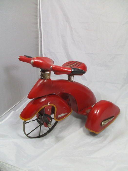 """Hierbij een mooie driewieler die gemaakt is uit onder andere hout en gietijzer. Deze is prachtig gedecoreerd met vooral rood en geel. Door de rode onderdelen heeft deze ook wat weg van een motorfiets of futuristisch voertuig. Deze ook wel genoemde """"skybike"""" verkeerd in goede staat.  In aanwinst voor elk interieur. Deze meet 38 cm lang - 27 cm breed - 32 cm hoog.  wordt aangetekend verstuurd of opgehaald"""