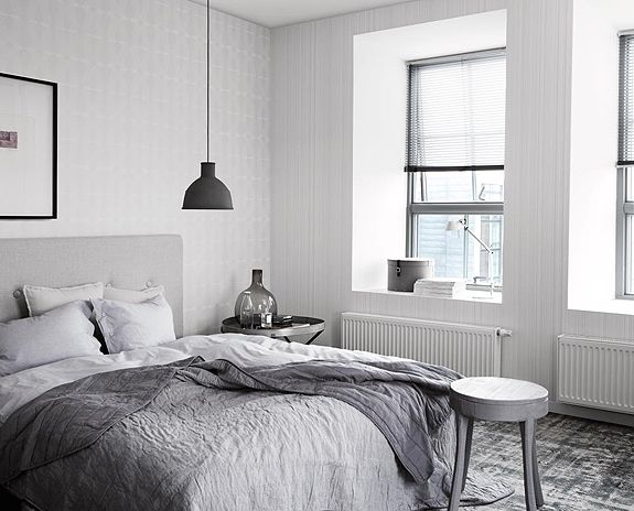 Muuto lamp in a grey and white bedroom, via The Design Chaser