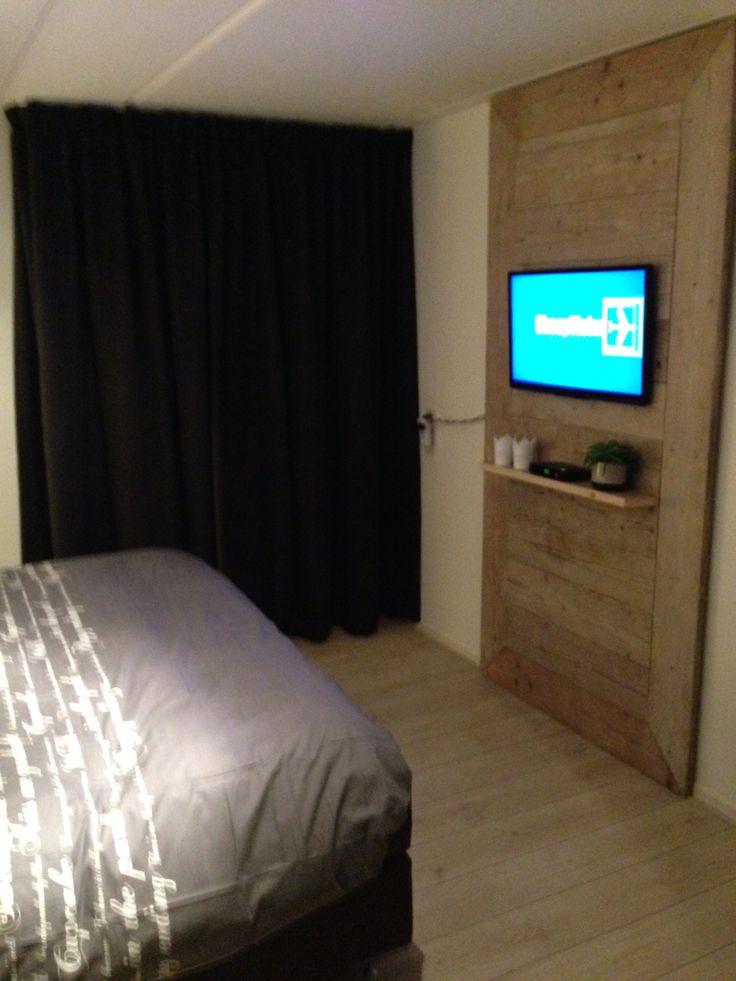 Slaapkamer met steigerhouten wand voor televisie