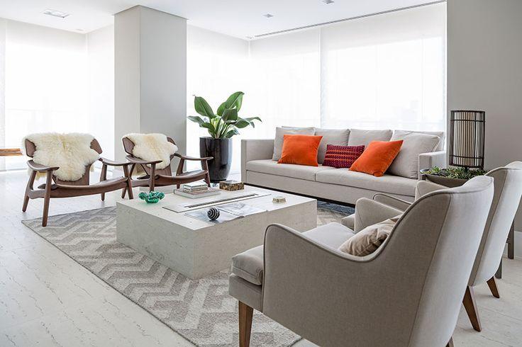 Sala de estar com poltronas de madeira, sofá branco, poltronas brancas, mesa de centro branca e luz natural.