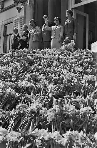 Typerend beeld van het defilé op Koninginnedag onder Juliana: bloemenhulde voor haar en haar gezin op de trappen van paleis Soestdijk