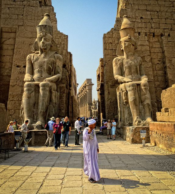 Colossal statues of Ramses II (19th Dynasty) wearing the Pshent crown flank the entrance to Luxor Temple. The double crown symbolizes the two regions of upper and lower Egypt.