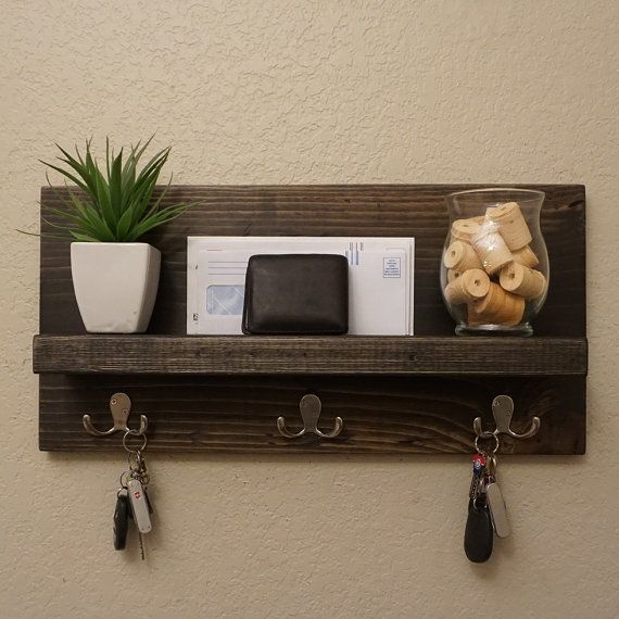 Handmade entryway shelf with satin nickel hooks. Perfect for any home entryway, apartment, or condo.  Made of solid wood. It has been lightly sanded down, then stained and sealed with a beautiful satin ebony finish.  This piece does not include the accessory items as shown in the pictures.  The color of the stained wood captured in the photos might vary slightly.  Dimensions: 23 in wide x 11 in tall x 4.25 in deep (shelf 3.5 in dp x 21 in lg)  Keyhole hangers are installed on the back with…