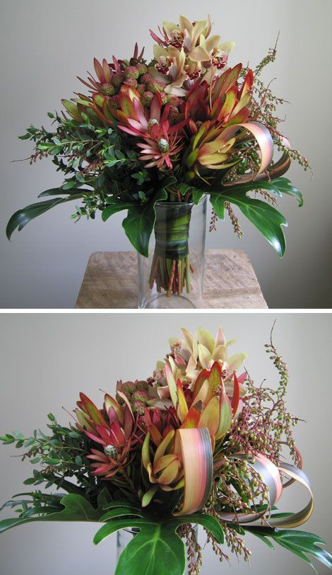 Exotic bouquet made with pale yellow/burgundy mini cymbidium orchids, Safari Sunset leaucadendron, blushing berzellia, andromeda, bonzai eucalyptus, tropical leaves, and striped flax leaf loops