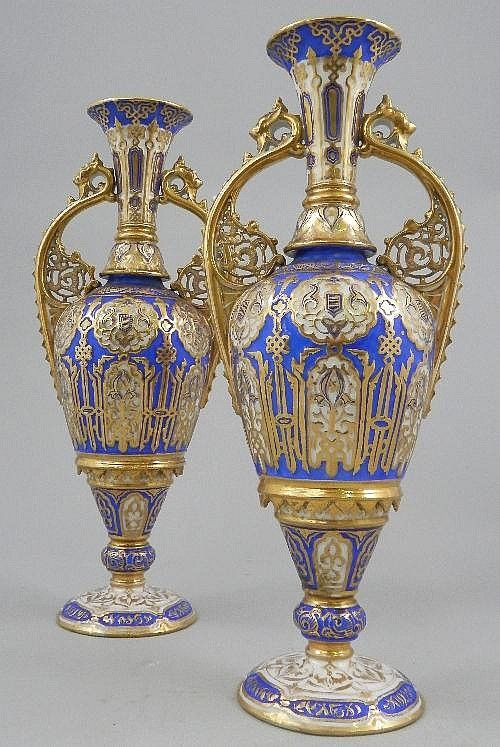 A pair of Russian Nicholas II twin handled vases, late 19th century, the tapering top leading to shoulders, pierced scrolling handles and tapering body above knop and circular foot, overall decorated with decorated panels and cartouches, heightened with gilding and fleur-de-lis, over blue and white ground, height 40 cm.