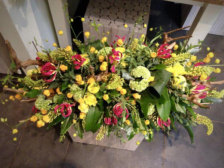 Kleurrijk rouwstuk met gezandstraalde takken #gloriosa #sandersonia #viburnum #rozen