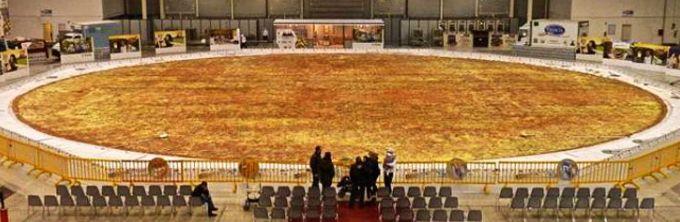 maior pizza do mundo ///Imagine que os italianos resolveram quebrar todas as regras: a maior pizza do mundo foi feita em 2012, com 40 metros de diâmetro e pesando mais de 17 toneladas! Eleita pelo Guiness como a maior pizza feita em todos os tempos, a receita demorou 48 horas para ficar pronta e na hora de ir para o forno precisou ser dividida em mais de 5 mil pedaços.