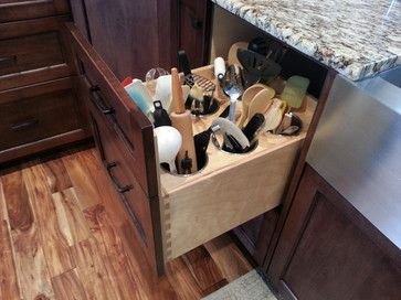 Store utensils in crocks. Not only do crocks keep wooden spoons, tongs and spatulas tidy, but they also keep tools close at hand so they're a cinch to grab when you need them. Of course, you could always take it one step further: built-in receptacles in a pullout drawer.