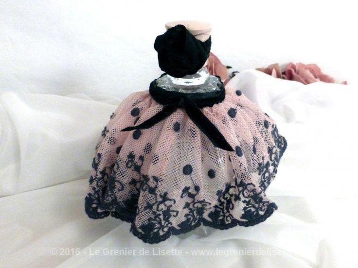 Flacon, tout en verre à facettes, et habillé de dentelle rose et noire avec son ruban en velours assorti.