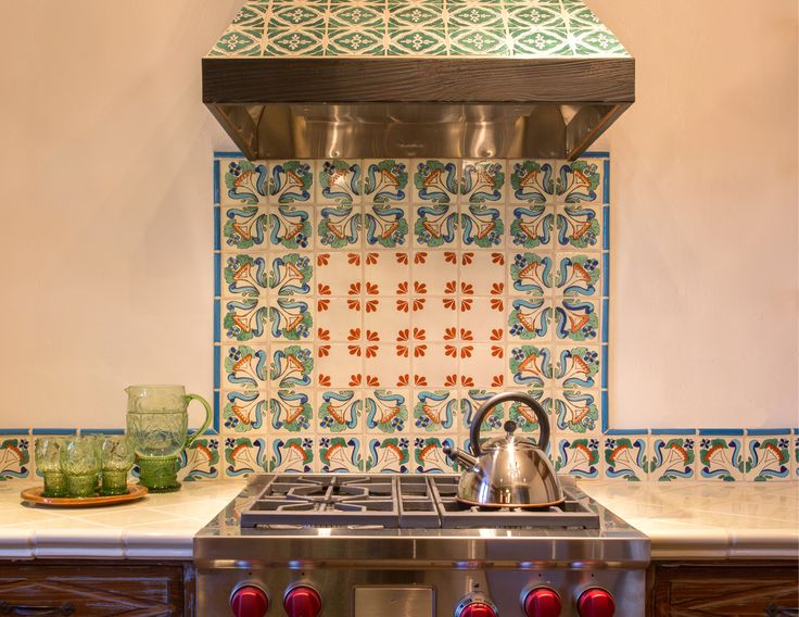 Kitchen by Statements Photo of a small southwestern l-shaped enclosed kitchen in Albuquerque with a farmhouse sink, raised-panel cabinets, beige cabinets, tile countertops, multi-colored backsplash, terra-cotta backsplash, stainless steel appliances, brick floors and an island. — Houzz