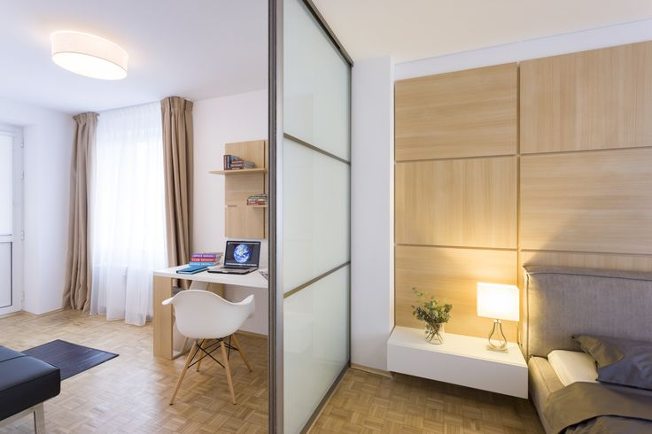 Bedroom and office in a 3 rooms apartament in Bucharest. The floor stays vintage, the furniture white with wood accents and a great wood wall. Perfect modern chair for a great home.