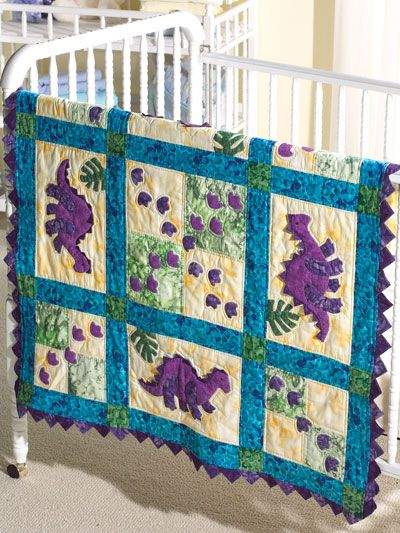 My Dinosaur Baby Quilt- The footprints of friendly little stegosaurs trail across an appliqued quilt finished with a prairie-point border.