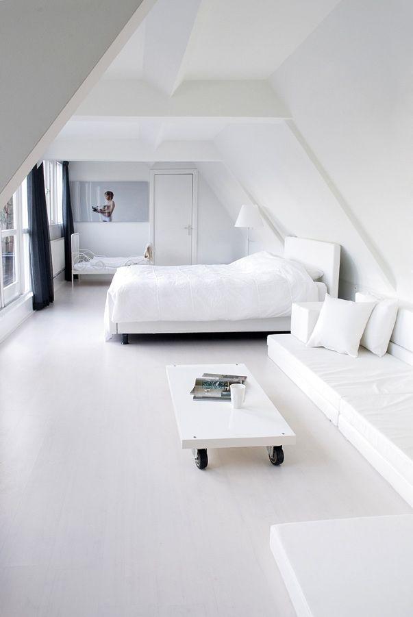 Biała sypialnia, styl minimalistyczny. Białe wnętrze, białe łóżko, biała pościel, białe poduszki, granatowe zasłony - http://www.mkstudio.waw.pl/