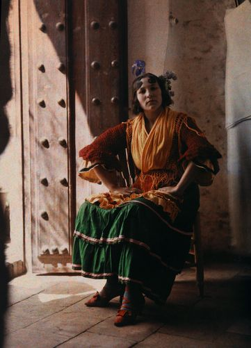 A gypsy sits in a chair in traditional clothing, Granada, Spain by Gervais Courtellemont, National Geographic