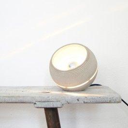 Betonleuchte aus rohem Beton mit Lightbeam. Diverse Farbvarianten sind durch Pigmentierungen möglich. Die Lampe ist eine abgestufte, fast geschlossene Kugel. Das Licht tritt durch die untere Öffnung heraus. Der Betonkörper wird von einem umlaufenden Plexiglasring unterbrochen durch den das Licht nach außen scheint. Eine Abflachung, schräg an der Oberseite, macht es möglich, dass man sie auch hinstellen kann. Die Lampe wird mit einer goldenen Metallfassung und einem Textilkabel geliefert. Die…