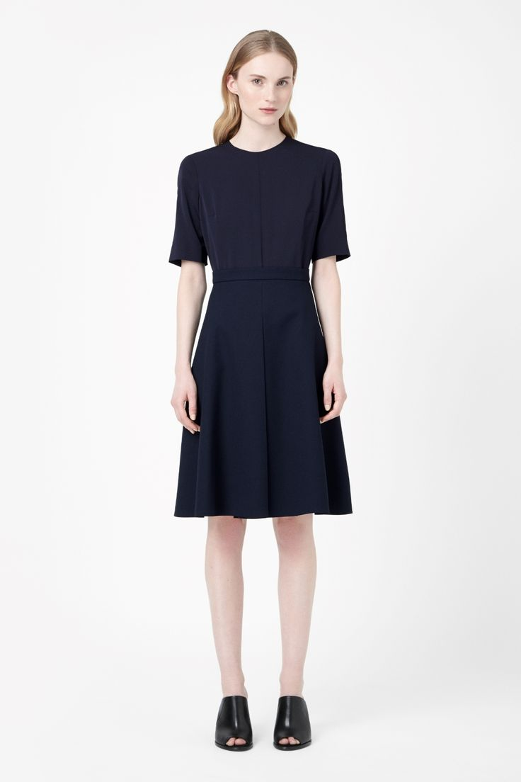 This short-sleeved dress has a textured pleated skirt for a flared shape and subtle tactile contrast. Fitted at the waist, it has an elegant wide neckline, hidden back zip fastening and a clean raw-cut hemline.